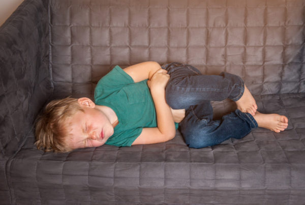 Depicting a child suffering from chronic pain on a couch.